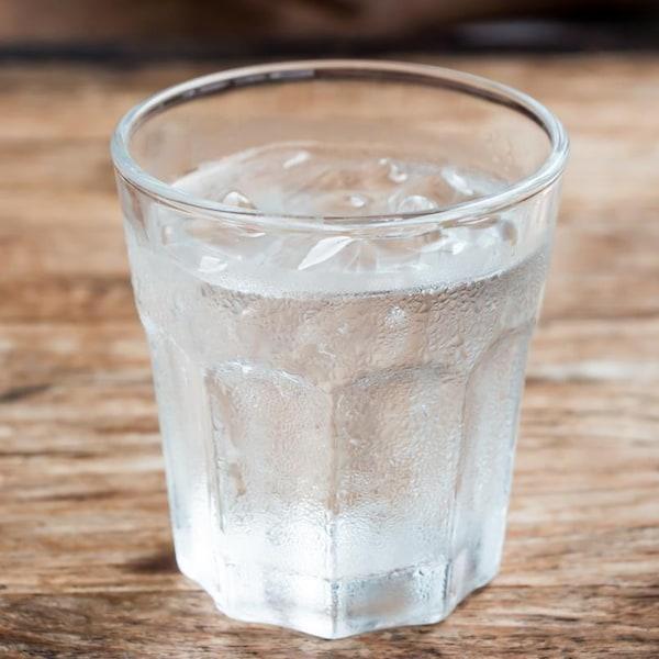 Le verre est posé sur une table en bois.
