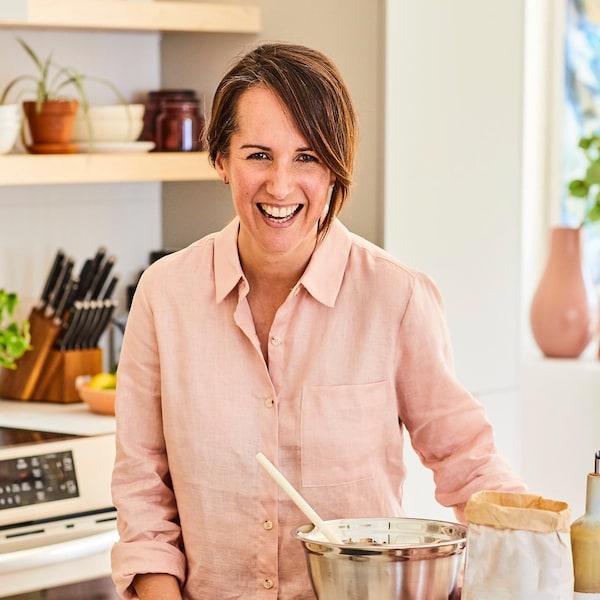 Geneviève O'Gleman prépare un dessert et devant elle plusieurs ingrédients sont visibles : sac de farine, cannelle, huile, poudre de cacao, etc.