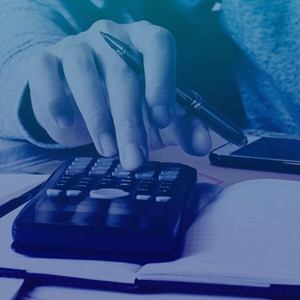 les mains d'une personne qui compte ses factures avec une calculatrice