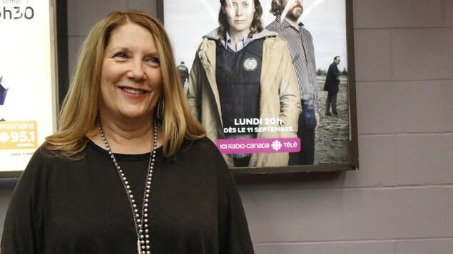 L'auteure pose devant l'affiche de la série Faits divers