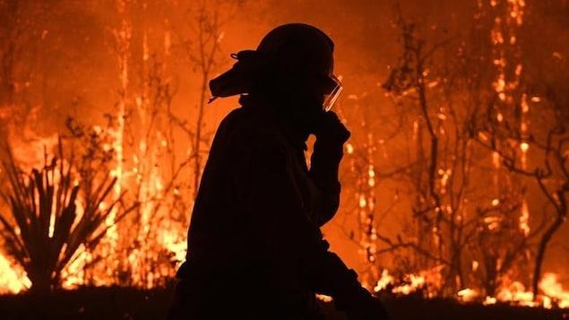 Un pompier marchant avec des flammes derrière lui.