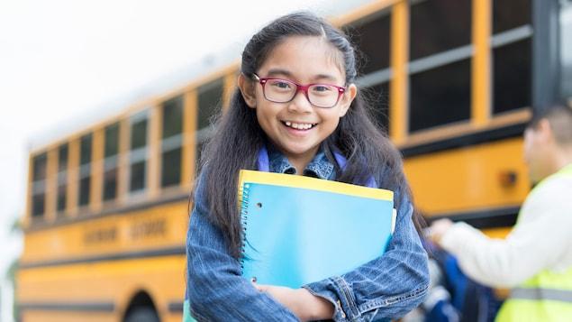 Une jeune fille avec ses articles scolaires.