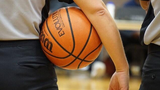 Un garçon qui tient un ballon de basketball.