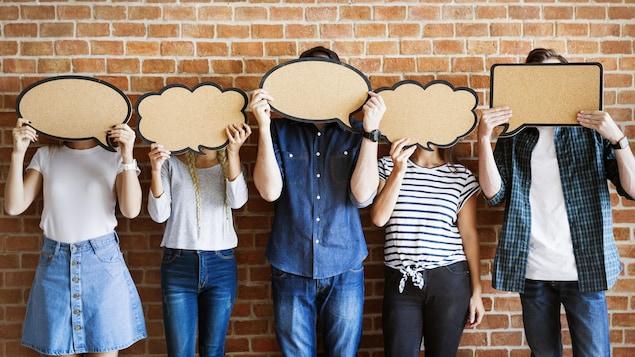 Des gens qui tiennent des bulles de texte devant leur visage.