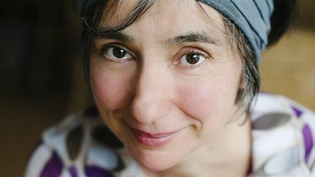 Portrait en couleur, en plan rapproché, en légère plongée, de Suzanne Myre. La femme sourit, regarde la caméra et porte un foulard sur ses cheveux.