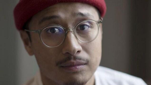 Portrait en couleur d'un jeune homme portant une tuque rouge, des lunettes rondes, une fine moustache et un bouc.