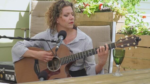 Alexis Normand à la guitare, sur une terrasse extérieure.
