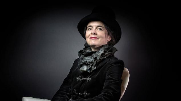 Une femme vêtue d'un veston et d'un chapeau noir prend la pose pour la caméra, assise sur un fauteuil.