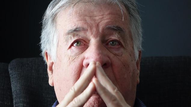 André Castonguay qui pleure avec les mains dans le visage.