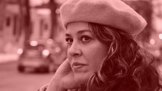 Portrait de la chanteuse Andrina Turenne dehors devant une rue où circulent des voitures.