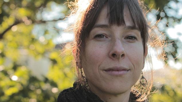 Portrait de la poète Anne-Marie Desmeules en extérieur, légèrement en contre plongée, avec le feuillage d'un arbre en arrière plan. Elle a les cheveux attachés et porte une frange et des boucles d'oreille.
