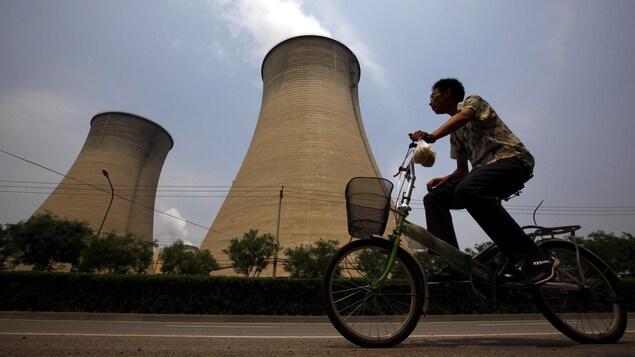 Un homme passe en vélo devant deux grandes cheminées d'où sort une fumée polluée.