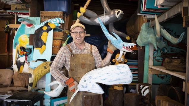 Maurice Sherwood avec deux sculptures dans les mains.