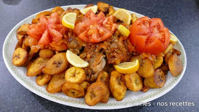 Dans une assiette de service, le poulet et les bananes plantains frites avec un décor de tomates fraîches et des quartiers de citron.