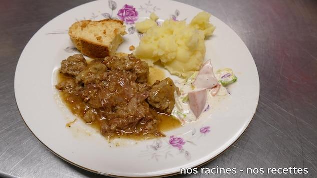 Sur le comptoir, une assiette de ragout de boulettes avec une purée de pommes de terre et du pain.