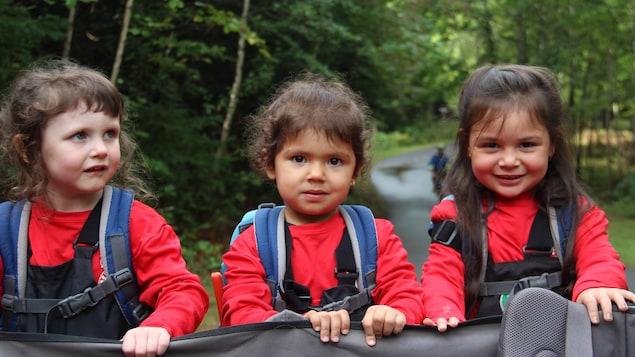 Trois petites filles posent dans la forêt
