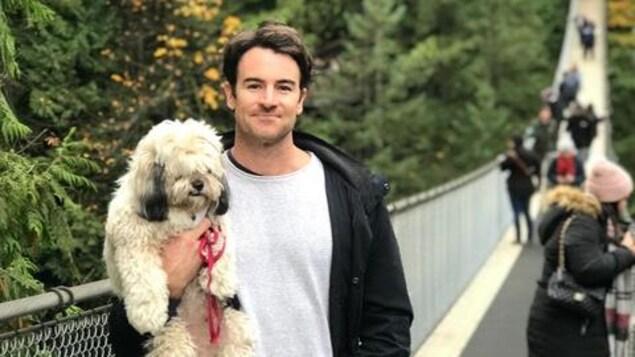 Un jeune homme tient un chien dans ses bras et se trouve sur un pont suspendu.