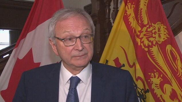 Blaine Higgs à l'Assemblée législative devant des drapeaux du Nouveau-Brunswick et du Canada.