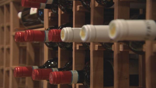 Des bouteilles de vin rangées dans une étagère.