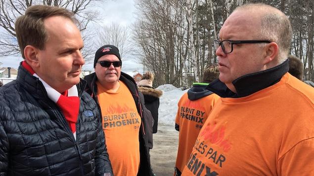 Steven MacKinnon parle avec un fonctionnaire fédéral vetû d'un gilet orange portant l'inscription «brûlés par Phénix».