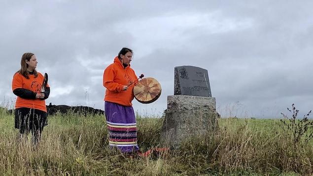 Deux Autochtones portant une plume et un tambour se recueillent devant une tombe.