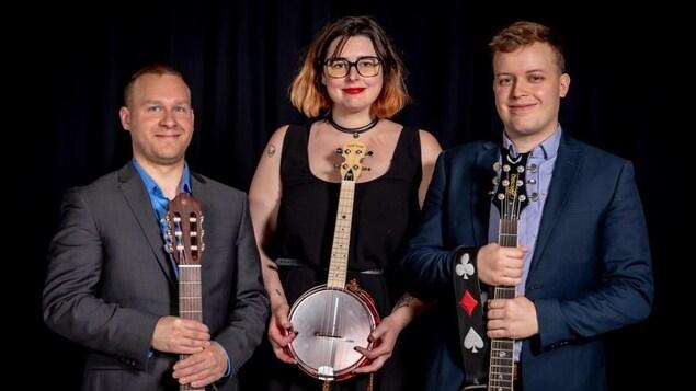 Thomas Chevalier, éemi et Philippe Gabriel posent pour une photo officielle. Thomas Chevalier et Philippe Gabriel tiennent dans leurs mains une guitare. éemi tient dans les siennes un banjo.