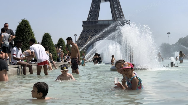 Des enfants et des adultes profitent de la fraîcheur des bassins du Trocadéro.
