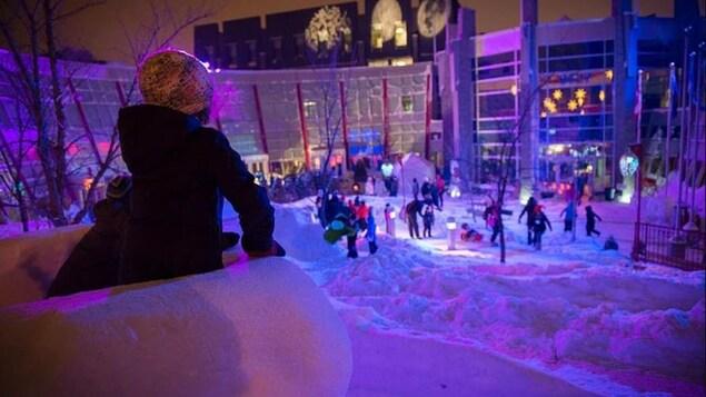 Vue de la cour extérieure de la Cité francophone à Edmonton lors du Flying Canoë Volant : éclairage de couleur, des enfants sur un belvédère en neige regardent plus bas où il y a des personnes qui s'amusent.