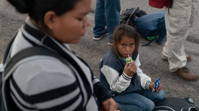 Une jeune migrante du Honduras est agenouillée au sol et boit un jus.