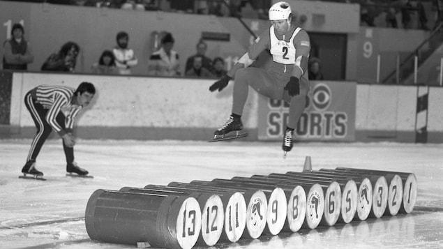 Un patineur tente de survoler 13 barils alignés sur la glace. Un arbitre penché, en retrait, regarde attentivement son saut. La foule est debout, attentive, dans les gradins. L'athlète est suspendu dans les airs comme un vrai ninja du patin!