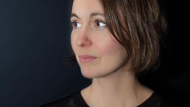 Portrait en couleur sur fond noir. La jeune femme ne regarde pas l'objectif, elle a le visage tourné de trois-quarts vers la droite. Elle porte un haut noir et des cheveux châtains au carré lâchés.