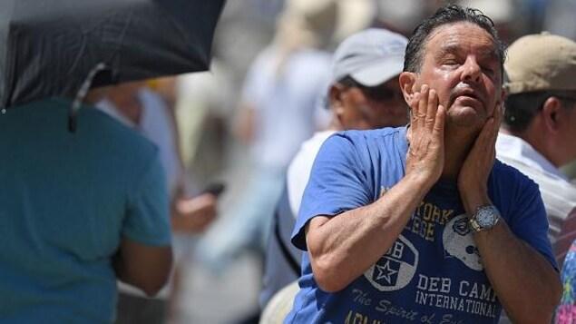 Un homme se rafraîchit à une fontaine publique.
