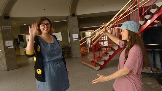 Les deux femmes sont dans le hall de La Cité Francophone pour quelques pas de danse. éemi salue la caméra de la main.