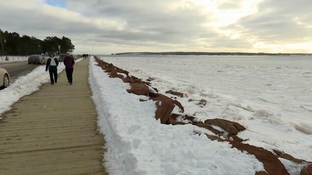 Des gens marchent sur un trottoir de bois bordant la route à deux pas de la mer