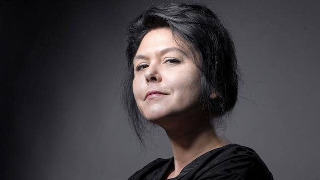 La femme habillée de noir pose en regardant le photographe avec un petit sourire.