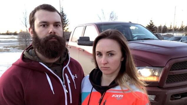 Le couple se trouve devant leur véhicule réparé.