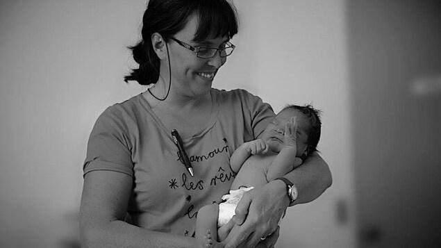 Christine Roy avec un nouveau-né dans ses bras
