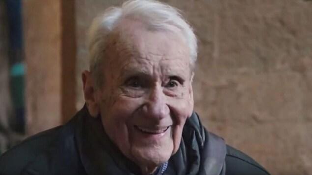 Un vieil homme sourit.