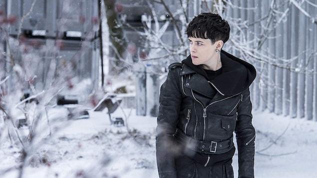 Claire Foy regarde sur le côté tout en marchant ans la neige.