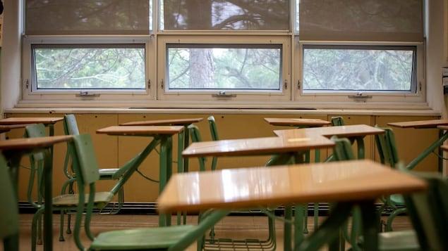 Une classe vide remplie de pupitres.