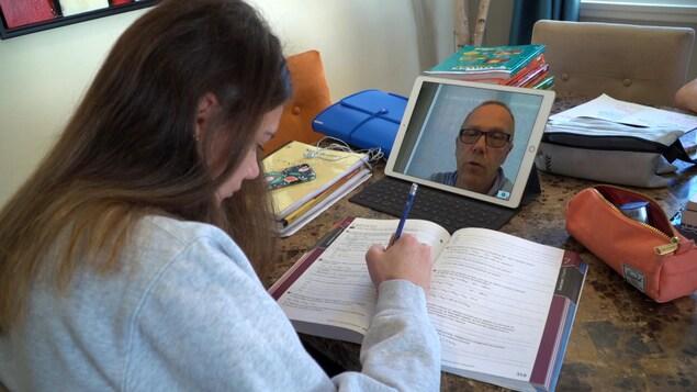 Une élève du Séminaire des Pères Maristes à Québec qui écoute son enseignant sur une tablette électronique pendant qu'elle réalise des exercices.