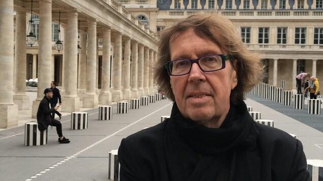 Le poète regarde dans l'objectif de l'appareil photo, les bras croisés, dans la cour intérieure du Palais-Royal, à Paris.