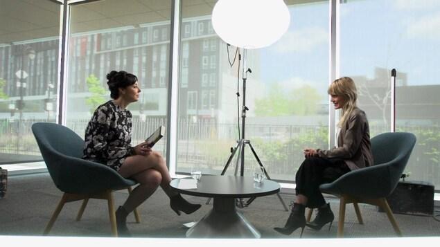 Les deux femmes sont assises l'une en face de l'autre dans un espace intérieur devant une grande vitre et un projecteur.