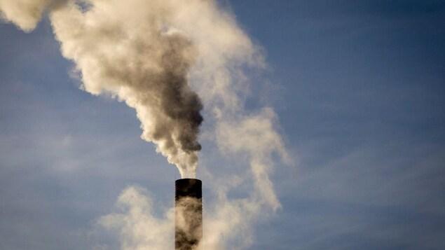 Une cheminée crache une épaisse fumée.