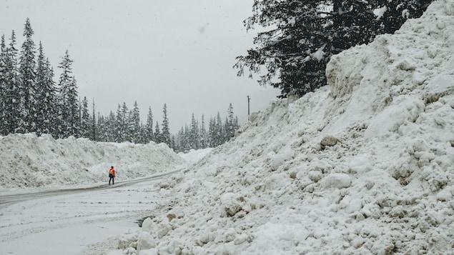 Une personne marche sur une route bordée de gros bancs de neige.