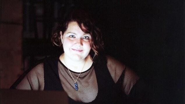 Sage Lovell sourit devant un écran d'ordinateur allumé.