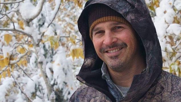 Le cinéaste sourit devant des arbres recouverts de neige.