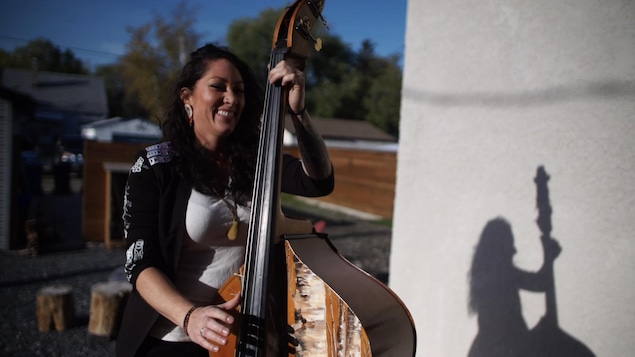 L'artiste métisse Marie-Josée Dandeneau joue de la contrebasse en plein air.