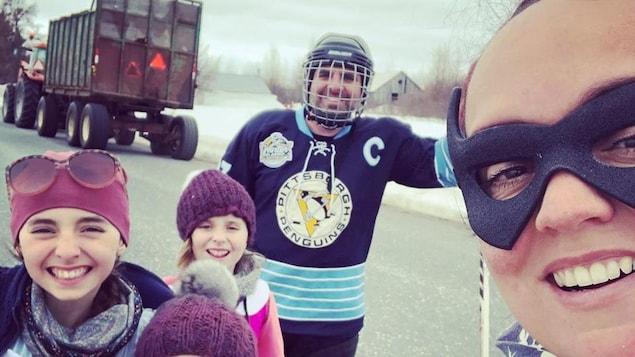 Guillaume Auger-Rivest ,sa femme et leurs trois filles sur une route. Guillaume est déguisé en joueur de hockey des Pingouins de Pittsburgh et sa femme porte un masque noir autour des yeux.