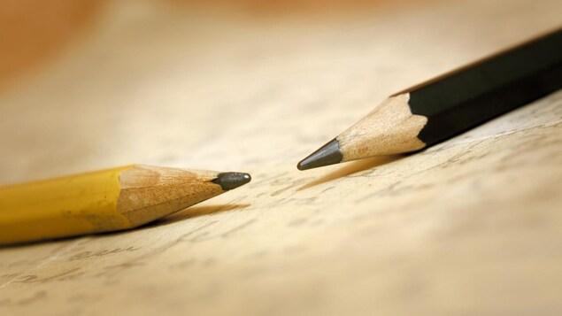 Deux crayons de bois sur un papier jauni.